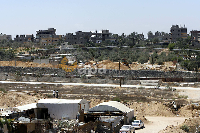 A view of tents covering the smuggling tunnels along the Egypt-Gaza border is seen from Rafah, southern Gaza Strip, on August 22, 2012, as Egyptian soldiers destroy the infrastructure of the tunnels on the Egyptian side of Rafah, since sources in Cairo suggested some of the gunmen from the attack on Egyptian troops in northern Sinai on August 8, that killed 16 soldiers, had entered Sinai through the tunnels. The tunnels trade, which analysts estimate is worth half a billion dollars a year, brings a wide variety of goods, including food, fuel and building materials, into the coastal territory which has been under an Israeli blockade since 2006.  Photo by Eyad Al Baba