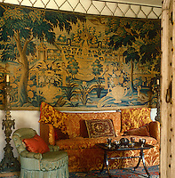 Detail of a tapestry and a sofa covered in etched orange velvet in the hall at Nymans