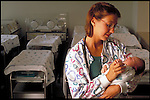 nurse holding newborn infant in hospital nursery