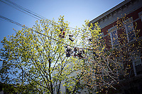 Sneakers hang from telephone wires in the Bushwick neighborhood of Brooklyn in New York on Saturday, April 27, 2013. The neighborhood is undergoing gentrification changing from a rough and tumble mix of Hispanic and industrial to a haven for hipsters, forcing many of the long-time residents out because of rising rents.. (©Richard B. Levine)