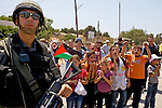 Palestinian children mock an Israeli border police officer during a non-violent demonstration in the West Bank village of An Nabi Salih near Ramallah on 09/07/2010.