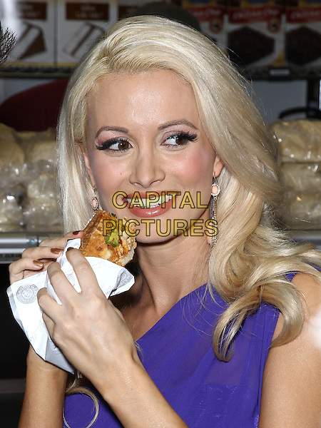Holly Madison.Earl of Sandwich Grand Opening Celebration with Holly Madison at The Palms Casino Resort,  Las Vegas, Nevada, USA..July 2nd, 2012.headshot portrait purple sandwich purple food eating.CAP/ADM/MJT.© MJT/AdMedia/Capital Pictures.