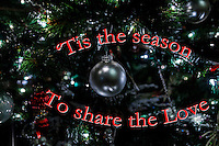 Close-up of Christmas tree ornatment with text in red - 'Tis the season   To share the Love.