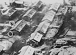 Aerial photos made from low-flying unarmed U.S. Air Force jet reconnaissance planes revealed these barracks-type structures near Chiktong in North Korea, which are believed to house enemy-held UN war prisoners. This enlarged section shows soldiers, some waving, others just looking at the aircraft overhead. Their true identity is a mystery. Structures who no markings which the Communist officials promised to use on all camps housing prisoners of war. March 1952.