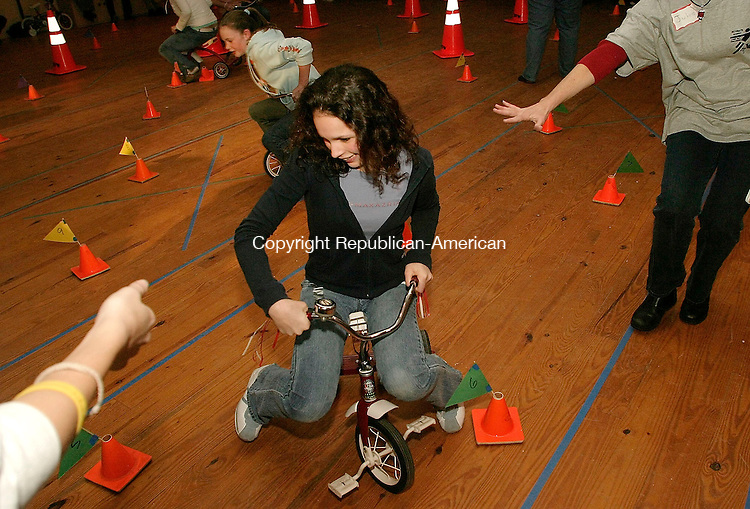 , CT- 27 FEBRUARY 2005-022705J03-Lexi Novak, 15, of Woodbury, rides a tricycle in the first leg of a relay during 'Ultimate Games' held Sunday at the Voegli Miniature Horse Farm in Woodbury. The event, in which local high school students face off in a series of challenges, was sponsored by the Woodbury's church communities and presented by St. Teresa of Avila Church. --- Jim Shannon Photo--St. Teresa of Avila Church; Lexi Novak; Voegli Miniature Horse Farm; Woodbury are CQ
