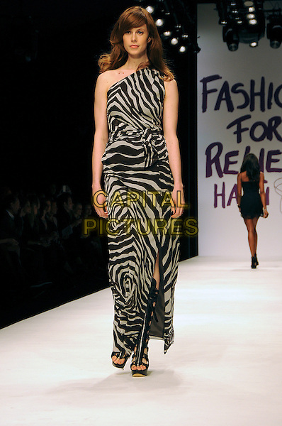 MODEL.The Fashion For Relief Haiti 2010 show for London Fashion Week Autumn/Winter 2010 at Somerset House, London, England..February 18th, 2010.LFW catwalk runway full length black dress white grey gray one shoulder zebra animal print maxi.CAP/CAS.©Bob Cass/Capital Pictures.