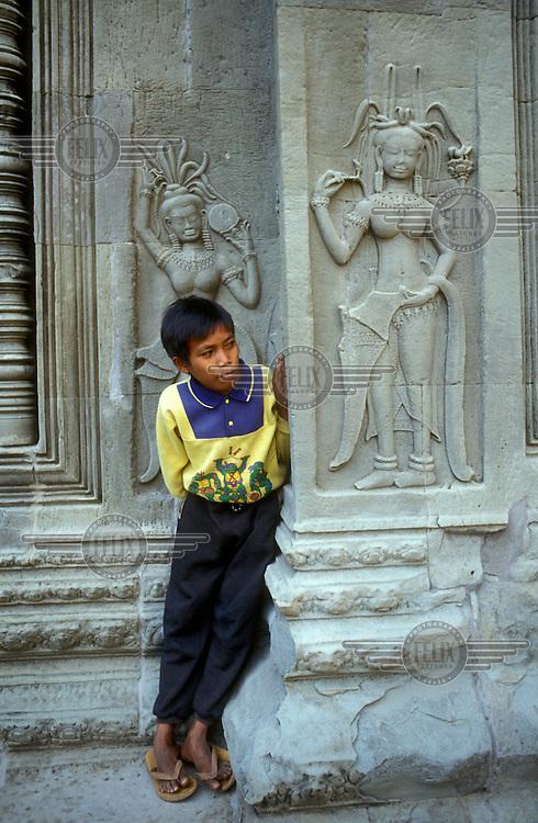 Boy playing hide-and-seek amongst the arcades of Angkor Wat Temple, beside figures representing divine dancing girls (apsaras or devatas).