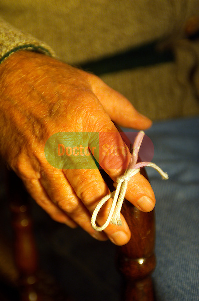 close-up of hand of elderly man with string tied on index finger as reminder