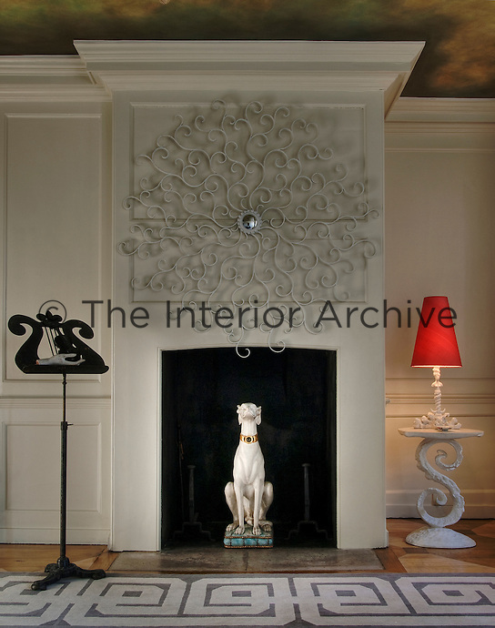 The drawing room chimney breast is dominated by an elaborate wrought iron  mirror and a statue