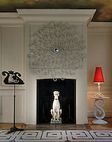 The drawing room chimney breast is dominated by an elaborate wrought iron mirror and a statue of a dog occupies the fireplace