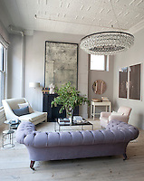 In the living room area the mirror, light fixtures, settee, and nesting tables are all by Ochre, the home-furnishing shop the couple owns