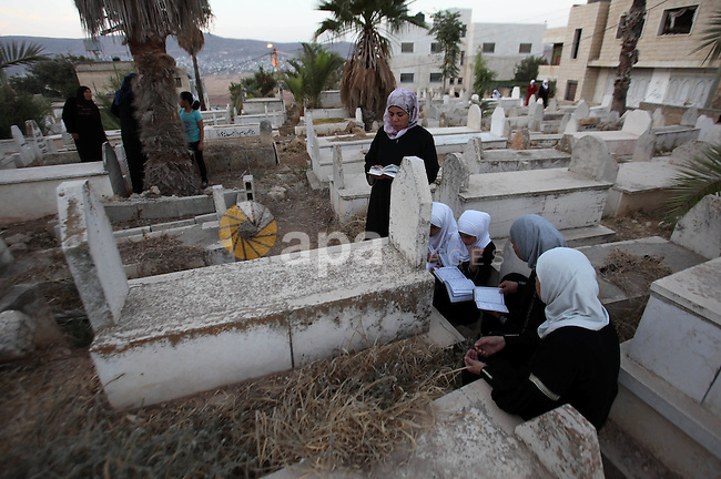 Palestinian women pray over the graves of relatives in a cemetery, on the Muslim holiday of Eid al-Adha or or the feast of sacrifice, in the West Bank City of Nablus on September 24, 2015. Muslims across the world are celebrating the annual festival of Eid al-Adha, or the Festival of Sacrifice, which marks the end of the Hajj pilgrimage to Mecca and in commemoration of Prophet Abraham's readiness to sacrifice his son to show obedience to God. Photo by Nedal Eshtayah