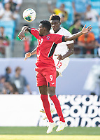 CHARLOTTE, NC - JUNE 23: Maykel Reyes #9 and Alphonso Davies #12 head the ball during a game between Cuba and Canada at Bank of America Stadium on June 23, 2019 in Charlotte, North Carolina.