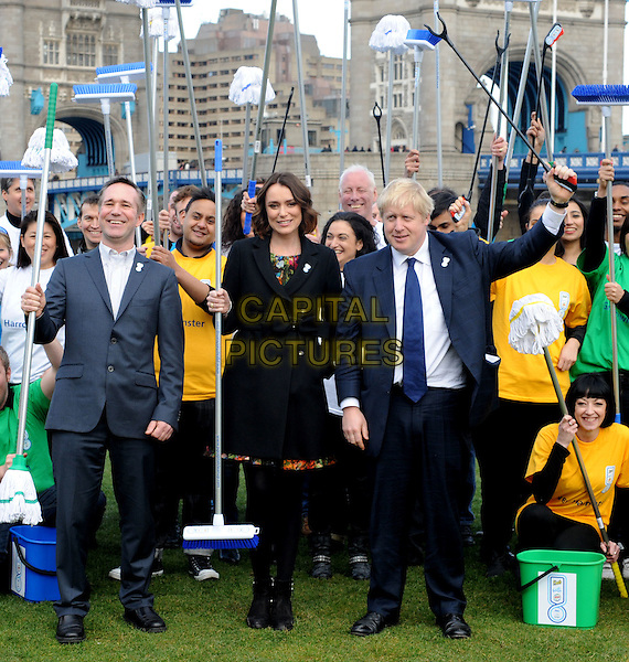 Keeley Hawes & Mayor Boris Johnson .The P&G Capital Clean Up launch campaign photocall, Potters Field Park, London, England..March 8th, 2012.full length black jacket suit blue tights coat bow ankle boots  broom MP  crowd cleaners brooms holding .CAP/WIZ.© Wizard/Capital Pictures.