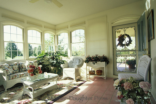 Sun Porch with wicker furniture and colorful flowers and textiles