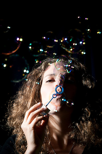 Cute female portrait.Blowing bubbles.