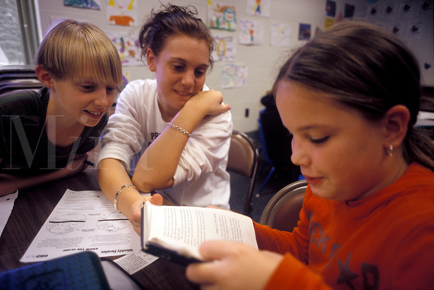 College student tutoring two girls in reading.