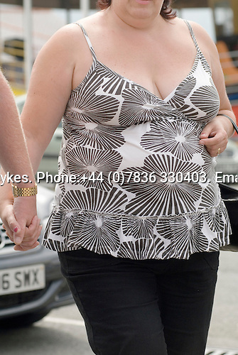 Ordinary obese young woman holding husband hand on holiday in Wales. Wearing floral paterned top. UK 2008