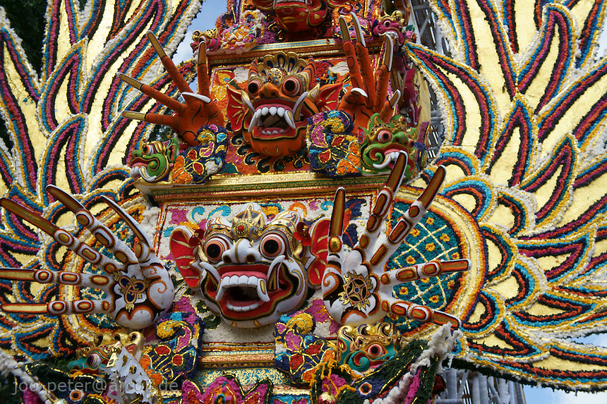 masks of protecting spirit Bhoma  with long fingernails and golden wings in a colorful decoration of the lower part of the huge and high tower-like carriage or sarcophagus called bade or wadah carrying reminders of the passed royal family member as part of cremation ceremonies, August 2011, royal capitol Ubud, Bali, archipelago Indonesia