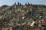 RUBBISH DUMP RECYCLING. South East Asia, Cambodia, Phnom Penh. Smokey Mountain, Steung Mean Chey, is Phnom Penh's municipal rubbish dump. Thousands work there, some 600 minors and 2000 adults, recycling the city's rubbish, dumped there by garbage trucks every day. The dump is notorious as many very young children work there. People eat and sleep overnight in the rubbish and fumes, under plastic tarpaulins or in the open air. They work 24 hours a day, like miners, with headlamps at night, collecting plastic, metals, wood, cloth & paper, which they sort and clean, weigh and sell, to be carried away for recycling. A day's work typically brings less than a dollar per person. One and a half to two dollars per day per family. The overpowering, acrid odour of grey smokey fumes blows across the dump, from which the place gets its name 'Smokey Mountain'. It can be smelt miles away. The shantytowns and squats, the recycling worker's homes butt onto or are inside the dump itself. There is no running water, sanitation and many are ill. Children often work with friends or relatives. Religious and ngo's help some children, but this is often resisted by families who need the extra income they generate.///Recycling workers collect materials on the fringes and ontop of Smokey Mountain