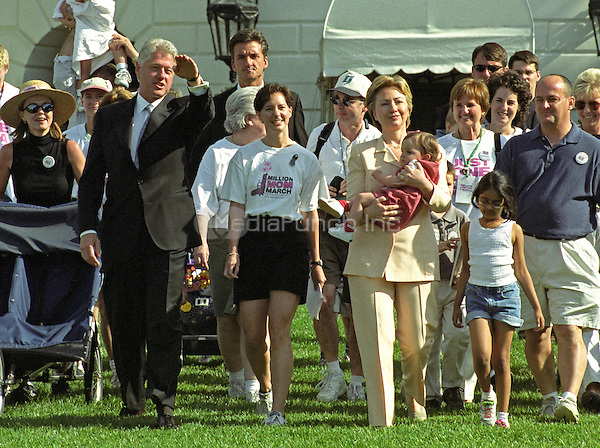 United States President Bill Clinton and first lady Hillary Rodham Clinton participate in the Million Mom March showing their support for stronger gun laws in the U.S. on the South Lawn of the White House in Washington, D.C. on May 14, 2000.  Also pictured are march organizer Christine O'Brien of Trenton, New Jersey, and her daughter Bridget, who is being carried by Mrs. Clinton.<br /> Credit: Ron Sachs / CNP/MediaPunch