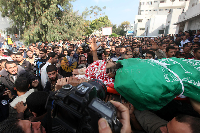Palestinians carry the body of a member of Hamas militant Ezz el-Deen al-Qassam brigades during his funeral  in Gaza City, on November 19, 2012. Media reports state that Israeli forces were on monday targeting the homes and other buildings occupied by Palestinian militants in its bombardment of the Gaza Strip, as the combined death toll in six days of airstrikes and rocket attacks climbed to nearly 100. Photo by Majdi Fathi