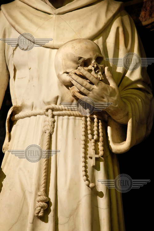 A sculpture of St Francis holding a skull in the Santa Chiara Basilica.