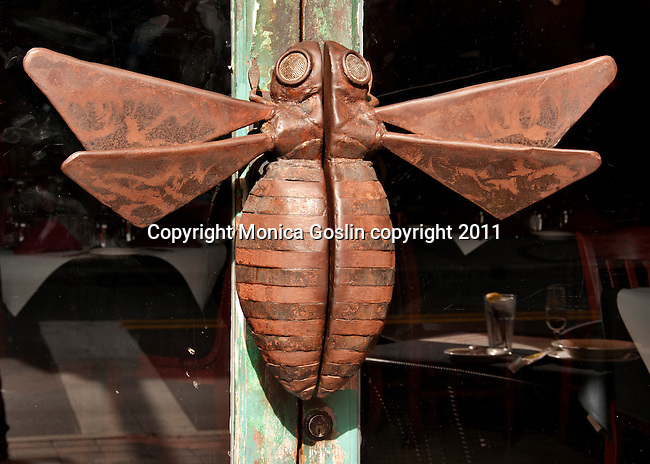 A restaurant's door with a large insect as the door handle in Ybor City, Florida