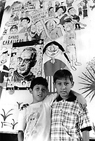 Two boys from the community of Nueva Esperanza standing in front of banner dedicated to the memory of monsignor Romero. El Despertar retreat centre, San Salvador, 1999.