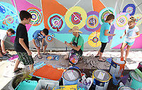 NWA Democrat-Gazette/DAVID GOTTSCHALK   Guest artist Matt Miller (center) prepares rollers and paint supplies Thursday, July 13, 2017, for students participating in the Street Art My Heart program for ages six through fourteen at the Arts Center of Ozarks in Springdale. Students spent the week going from sketches to conception creating a mural on the center's east exterior building wall.
