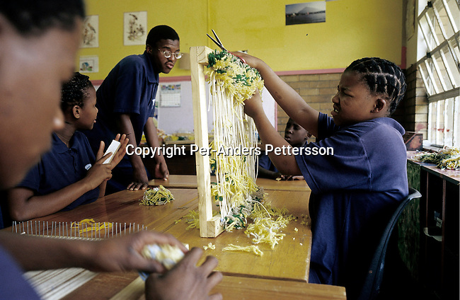 KLIPRIVER, SOUTH AFRICA APRIL 17: Jane Mokoena, age 19 (R), weave in a vocational class at Sibonile (means: we have seen) School for the Blind on October 13, 2003 in Klipriver, south of on April 17, 2003 after taking a shower at Sibonile (means: we have seen) School for the Blind in Klipriver, south of Johannesburg, South Africa. A blind woman founded the school in 1994. The school has about 125 students from disadvantaged communities around South Africa. Many of the children have faced rejection from their families and communities, and at Sibonile they have a chance for a good education. (Photo: Per-Anders Pettersson).