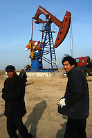 Workers at the Sinopec Petrochemical oil field in Puyang, Henan province, China. Farmers in the area often steal natural gas for cooking and heating. They steal the gas from the pipe-line filling a big plastic bag in an hour. As soon as one finishes filling a bag, another family will fill another bag, it goes on continuously. A bag of natural gas is enough fuel for up to one week..
