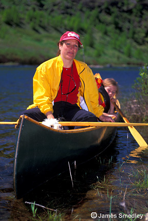 Mother paddling a canoe with her kids