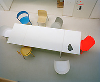 Aerial view of the long white dining table with a collection of Stefan Diez's chairs