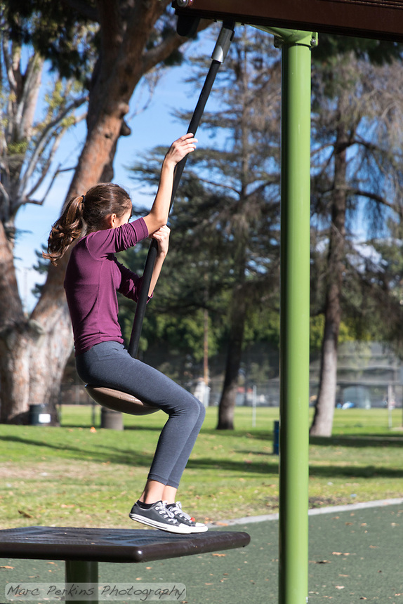 A girl prepares to swing down a play structure at South Gate Park.