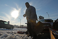 """Robert """"Bobbo"""" Conner, a Chicago public housing resident, shovels snow out from in front of a car in the parking lot in front of his building, a Cabrini Green high rise, on the Near North Side of Chicago, Illinois on December 18, 2007."""