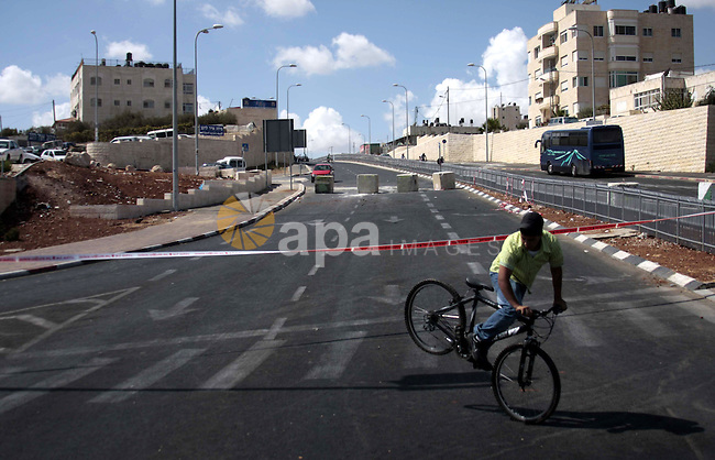 A young man rides his bicycle down an empty street in an East Jerusalem neighborhood on Yom Kippur, the Day of Atonement, Jerusalem, Israel on 28 September 2009. Yom Kippur is the holiest and most solemn in the Jewish calendar and religious Jews spend the day in prayer. Traffic is not allowed throughout Israel during the day and children and secular Jews take time to explore the city on their bicycles. Photo by Mohamar Awad
