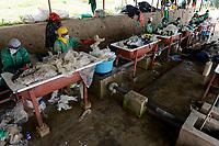 RWANDA, Kigali, plastic recycling at company ecoplastics, worker clean with solvent old plastic foils before processing to granulate which is used for new plastic products /  / RUANDA, Kigali, plastic recycling bei Firma Ecoplastics, Reinigung von alten dreckigen Folien mit Loesungsmittel , anschliessend Trocknung und Weiterverabeitung zu Plastik Granulat fuer neue Plastik Produkte
