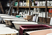 Reclaimed toilets and bath tubs at a salvage yard.