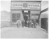 Front-end view of one-story store with false front lettered: Drug Store - POST OFFICE and DOCTOR CAHILL.  Windows lettered: DRUGS, MEDICINE - STATIONERY NOTIONS.  Hanging sign over boardwalk reads: DRUG STORE.  Five men are standing in front of store.<br /> Elizabethtown, NM  1899
