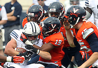 Brigham Young wide receiver JD Falslev (12) is tackled by a horde of Virginia  defenders during the first half of the game in Charlottesville, Va. Virginia defeated Brigham Young 19-16. Photo/Andrew Shurtleff