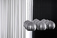 In a living room nine stainless steel pendant lights are suspended in front of a sheer white curtain