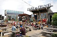 Nederland Amsterdam 2017 08 07. Broedplaats de Ceuvel in Amsterdam-Noord. Op de oude scheepswerf op de Buiksloterham is een wijk ontstaan van ontwerpers, bouwers en ondernemers; een stadse vrijhaven op een nog onontgonnen stuk Amsterdam. Het ontwerpteam van Jeroen Apers, Steven Delva, Sascha Glasl, Marjolein Smeele en Wouter Valkenier won in 2013 een wedstrijd die was uitgeschreven door stadsdeel Noord. Dat zocht een goed plan om het terrein van de oude scheepswerf De Ceuvel-Volharding, met zwaar verontreinigde grond, een nieuwe bestemming te geven. Het team verzon een verrassende oplossing: woonboten, vaak afgedankt en goedkoop, werden op de vervuilde grond geplaatst. Zo hoefde er niet te worden geheid of gegraven. Inmiddels staan er zestien woonboten, verbonden door een lange houten steiger om de boten heen loopt. De planten en bomen rondom de boten zorgen voor reiniging van de grond. In de woonboten zijn bedrijfjes gevestigd. Cafe de Ceuvel.  Foto Berlinda van Dam / Hollandse Hoogte