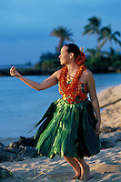 Young woman with lei and ti leaf skirt making a pua (flower) during an auana hula dance on the beach