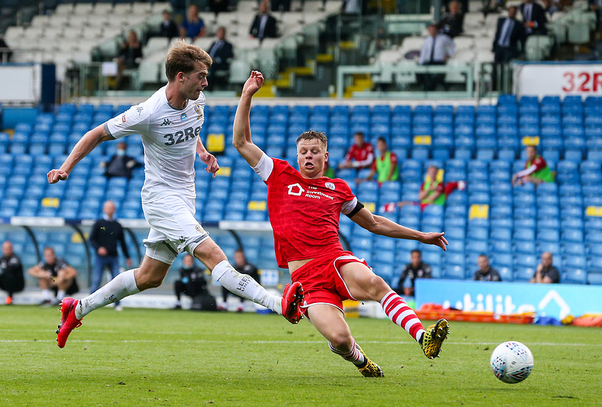 Leeds United's Patrick Bamford shoots under pressure from Barnsley's Mads Juel Andersen<br /> <br /> Photographer Alex Dodd/CameraSport<br /> <br /> The EFL Sky Bet Championship - Leeds United v Barnsley - Thursday 16th July 2020 - Elland Road - Leeds<br /> <br /> World Copyright © 2020 CameraSport. All rights reserved. 43 Linden Ave. Countesthorpe. Leicester. England. LE8 5PG - Tel: +44 (0) 116 277 4147 - admin@camerasport.com - www.camerasport.com