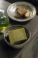 Handmade soap  in makeshift soapdishes fashioned out of a tin cup and saucer