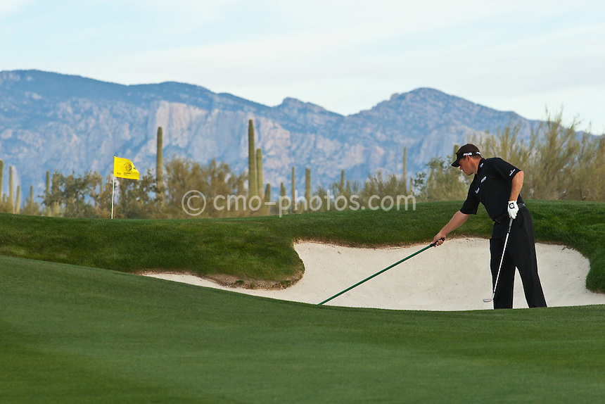 Feb 23, 2009; Marana, AZ, USA; Lee Westwood (ENG) rakes a bunker on the 8th hole during a Monday practice round prior to the World Golf Championships-Accenture Match Play Championship at the Ritz-Carlton Golf Club, Dove Mountain.