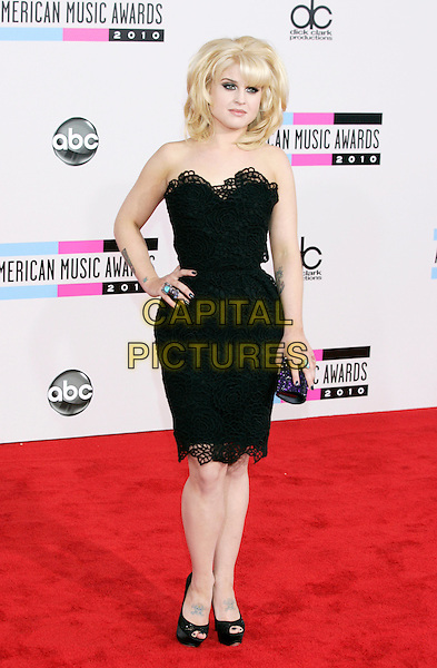 KELLY OSBOURNE.Arrivals  to the 2010 American Music Awards held at Nokia Theatre L.A. Live in Los Angeles, California, USA..November 21st, 2010.AMA AMAS AMA'S full length dress hand on hip strapless black cut out lace peep toe platform shoes rings ring turquoise blue clutch bag .CAP/PE.©Peter Eden/Capital Pictures.