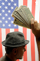 Man hand raised with US dollars on US flag (Licence this image exclusively with Getty: http://www.gettyimages.com/detail/85071273 )