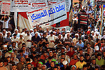 "Supporters of the Muslim Brotherhood pray during a protest in support of ousted president Mohamed Morsi, outside Rabaa al-Adawiya mosque in Cairo, Egypt, July 29, 2013. Deadly clashes broke out during funerals of slain supporters of Egypt's ousted Islamist president Sunday, as the supreme leader of the Muslim Brotherhood urged his followers to stand fast after more than 80 of them were killed in weekend violence. The Arabic reads, ""Yes for the legitimacy, no for the coup."" . Photo by Ahmed Asad"